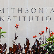 "Smithsonian National Museum of American History Sign and Flowers. The word's ""Smithsonian institution"" etched into the granite walls of the Smithsonian National Museum of American History in Washington DC. This sign, on the Mall side of the building, is framed by a small flower garden."
