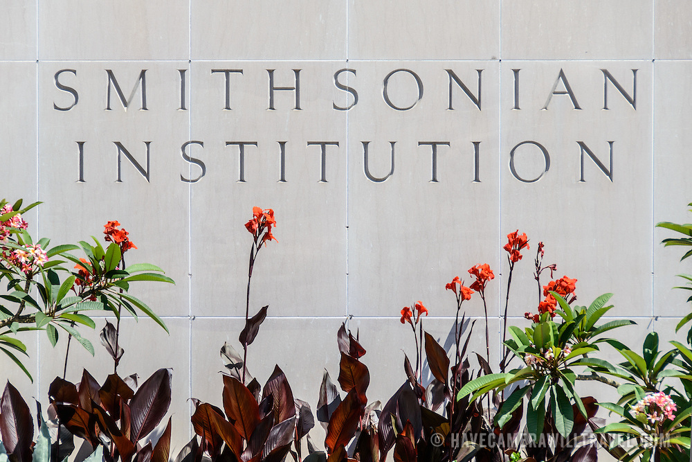 """Smithsonian National Museum of American History Sign and Flowers. The word's """"Smithsonian institution"""" etched into the granite walls of the Smithsonian National Museum of American History in Washington DC. This sign, on the Mall side of the building, is framed by a small flower garden."""