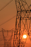 Transmission towrs and power lines silhouetted against the rising sun, Whatcom County Washington