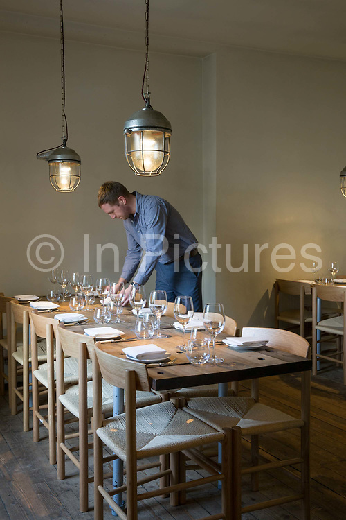 A male waiter setting a formal dinner table at Gardeners Cottage resturant on the 9th November 2018 in Edinburgh, Scotland in the United Kingdom.