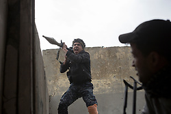 Licensed to London News Pictures. 01/04/2017. Mosul, Iraq. An Iraqi Federal Police RPG gunner shouts as he fires a rocket at an ISIS target from a West Mosul rooftop in Iraq today (01/04/2017). Iraqi forces continue to fight house to house as they push further into West Mosul. Iraqi forces are now advancing on the city's old districts where Islamic State fighters still hold out. Photo credit: Matt Cetti-Roberts/LNP