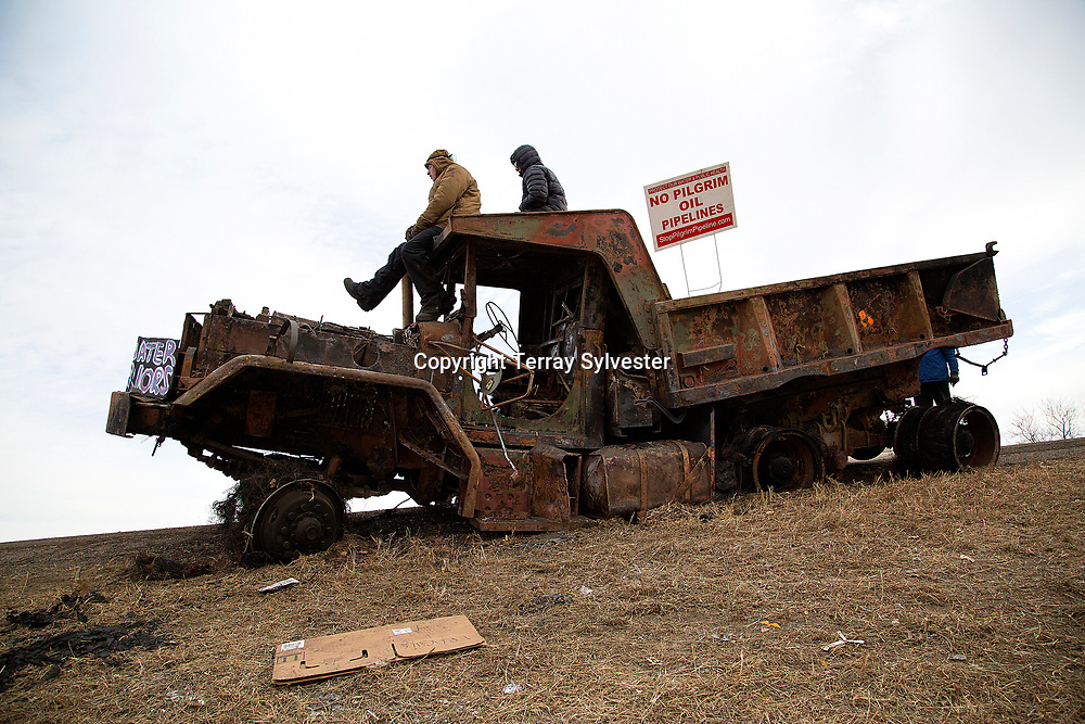 Opponents of the Dakota Access oil pipeline sit on a burned law enforcement truck after confrontations with police near the pipeline route on November 21, 2016. Cannon Ball, North Dakota, United States.