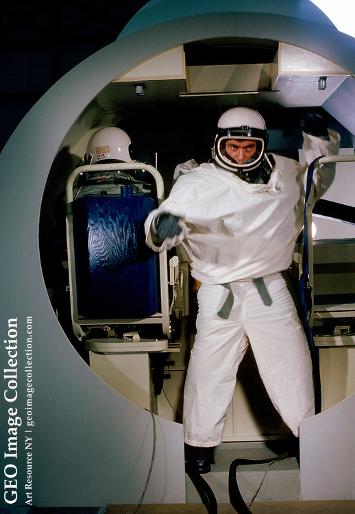 Space-suited test person practices maneuvers inside a training vehicle while another man sits in the trainer's chair.