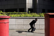 A businessman gets upright again while checking messages by an urban garden of bushes and shrubs.