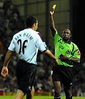 Photo: Ed Godden.<br /> Portsmouth v Bolton Wanderers. The Barclays Premiership. 25/09/2006. Referee Uriah Rennie (R) show Bolton's Tal Ben Haim the yellow card.