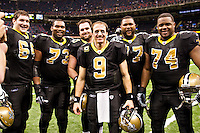 NEW ORLEANS, LA - DECEMBER 26:   Quarterback Drew Brees #9 and the offensive line of the New Orleans Saints pose after the game for a photo after Brees throws a nine-yard touchdown pass to running back Darren Sproles #43 and breaks the single-season passing record in the fourth quarter against the Atlanta Falcons at Mercedes-Benz Superdome on December 26, 2011 in New Orleans, Louisiana.  The Saints defeated the Falcons 45-16.  (Photo by Wesley Hitt/Getty Images) *** Local Caption *** Drew Brees Sports photography by Wesley Hitt photography with images from the NFL, NCAA and Arkansas Razorbacks.  Hitt photography in based in Fayetteville, Arkansas where he shoots Commercial Photography, Editorial Photography, Advertising Photography, Stock Photography and People Photography