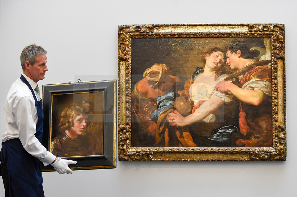 """© Licensed to London News Pictures. 28/06/2019. LONDON, UK. A technician carries """"Head of a Young Warrior"""", 1615-17, by Peter Paul Reubens (Est. GBP2.5-3.5m) in front of """"The Temptation of Saint Mary Magdalene"""" by Johann Liss (Est. GBP4-6m) at the preview of Sotheby's Old Masters sale which takes place at its New Bond Street galleries on 3 July.  Photo credit: Stephen Chung/LNP"""