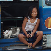 Young Indonesian girl sits in the door of her families van with her cat. Java, Indonesia.
