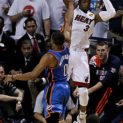 Jun 21, 2012; Miami, FL, USA; Miami Heat shooting guard Dwyane Wade (3) passes the ball as Oklahoma City Thunder point guard Russell Westbrook (0) defends during the third quarter in game five in the 2012 NBA Finals at the American Airlines Arena. Mandatory Credit: Derick E. Hingle-US PRESSWIRE