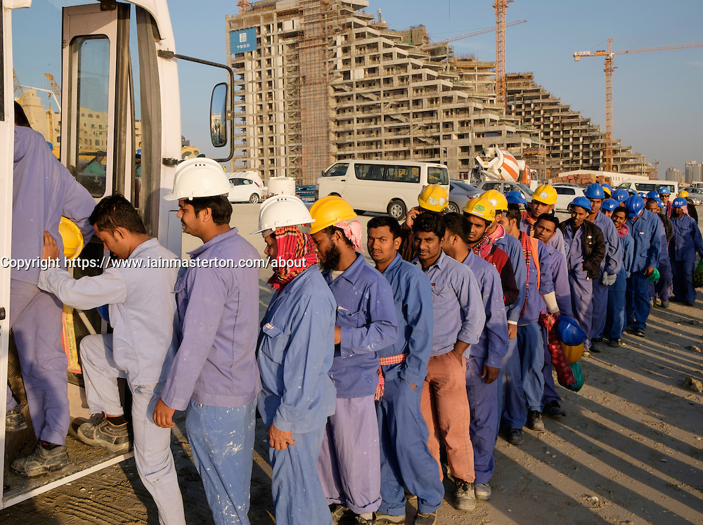 Construction workers queuing to get on bus to living quarters at end of working day in Dubai United Arab Emirates