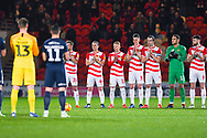Both sets of players, including goalkeeper Marko Marosi of Doncaster Rovers (13), hold a minute applause in honour of Gordon Banks during the EFL Sky Bet League 1 match between Doncaster Rovers and Southend United at the Keepmoat Stadium, Doncaster, England on 12 February 2019.