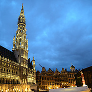 Ornate buildings in the Grand Place, Brussels, at dusk. Originally the city's central market place, the Grand-Place is now a UNESCO World Heritage site. Ornate buildings line the square, including guildhalls, the Brussels Town Hall, and the Breadhouse, and seven cobbelstone streets feed into it.