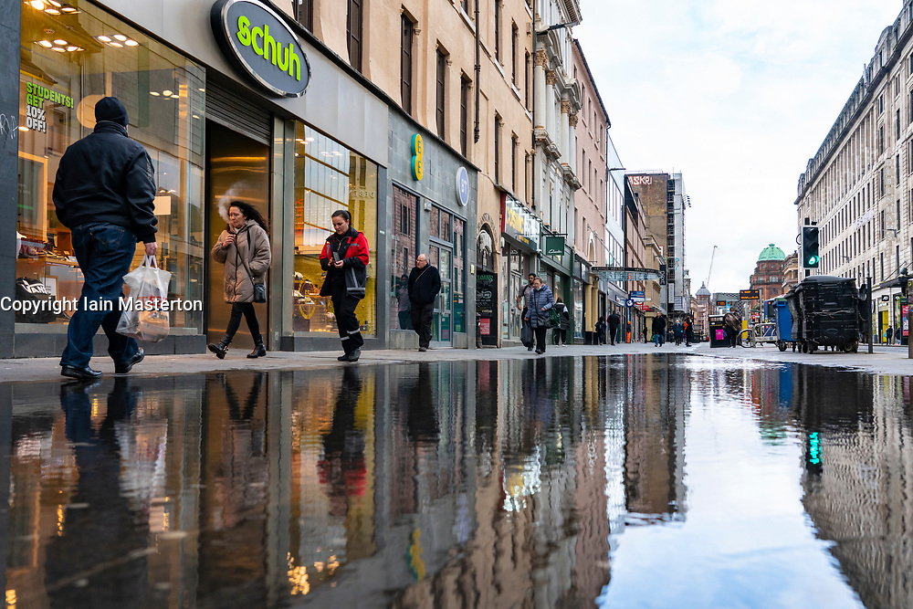 Glasgow, Scotland, UK. 12 March 2021. On the day Covid-19 lockdown is relaxed slightly in Scotland the city centre streets in Glasgow city centre remain almost deserted virtually all shops ad cafes are still closed. Pic;  Pubic are reflected in puddle in Argyle Street. Iain Masterton/Alamy Live News