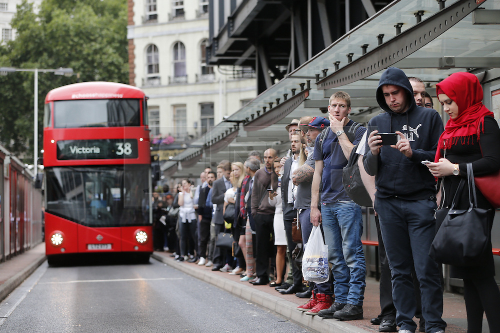 © Licensed to London News Pictures. 06/08/2015. London, UK. Commuters queuing for replacement buses outside Victoria Station during the tube strike on Thursday, August 6, 2015. The strike is a 27-hour stoppage by about 20,000 Tube staff to shut down the entire London Underground network  over pay and conditions for new Night Tube. Photo credit: Tolga Akmen/LNP