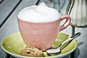 Cappuccino and cookie in pink cup with yellow saucer