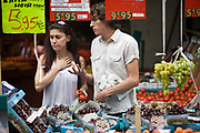A young couple choose vegetables on a market stall on the Rue Mouffetard.<br /> Rue Mouffetard is in the Fifth (cinquieme) arrondisement and the street is very old: originally a Roman rod running from the Roman Rive Gauche city south the Italy. The market is famous for it's quality fresh produce and artisanal food shops.