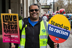 London, UK. 16th March, 2019. A steward hands out placards before the March Against Racism demonstration on UN Anti-Racism Day.