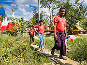 01 NOVEMBER 2015 - YANGON, MYANMAR: Supports of the NLD walk across a small creek to get to the NLD's last election rally of the 2015 election in the Yangon suburbs Sunday. Political parties are wrapping up their campaigns in Myanmar (Burma). National elections are scheduled for Sunday Nov. 8. The two principal parties are the National League for Democracy (NLD), the party of democracy icon and Nobel Peace Prize winner Aung San Suu Kyi, and the ruling Union Solidarity and Development Party (USDP), led by incumbent President Thein Sein. There are more than 30 parties campaigning for national and local offices.    PHOTO BY JACK KURTZ