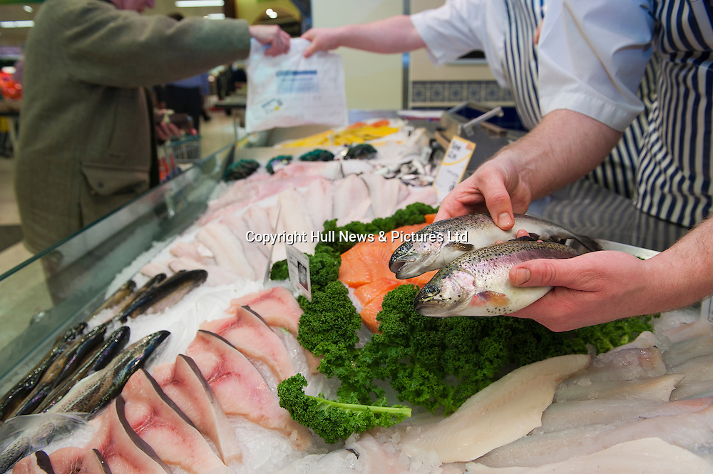 A fish monger holding two rainbow trout at the fish counter in a UK supermarket while a colleague serves a customer in the background.