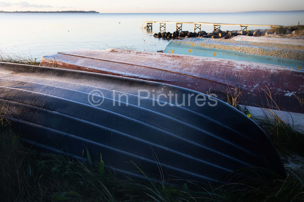 Upturned boats lie by the sea, October 29th 2019, Denmark. The coast along Århus Bugten is calm on an early autumn morning, shortly after sun rise. The first frost has arrived and small upturned rowing boats are covered in frost. It is out of season and the boats are ready for winter. The beach is nearly deserted and is between Århus and the neaby coal power plant Studstrup.