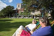 Two women sunbathing in gardens of the Priory Hotel, Wareham, Dorset, England, UK