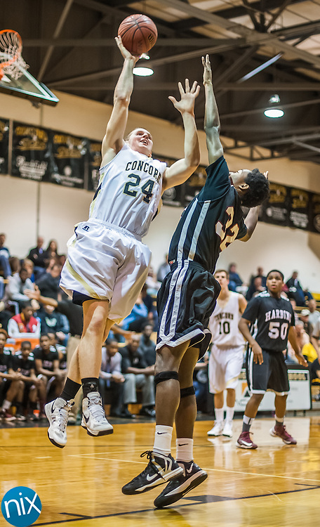 Concord's Reid Aube goes up for a shot against Harding's Emmanuel Patton during the third round of the NCHSAA 3A playoffs Friday night at Concord High School. Harding defeated the Spiders 71-65.