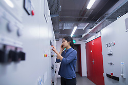 Young female engineer updating control panel using mobile phone in an industrial plant, Freiburg im Breisgau, Baden-Wuerttemberg, Germany