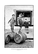 Young boys playing on beer barrels in Castlebar, County Mayo.<br /> <br /> 06/01/1952<br /> <br /> 6th January 1952