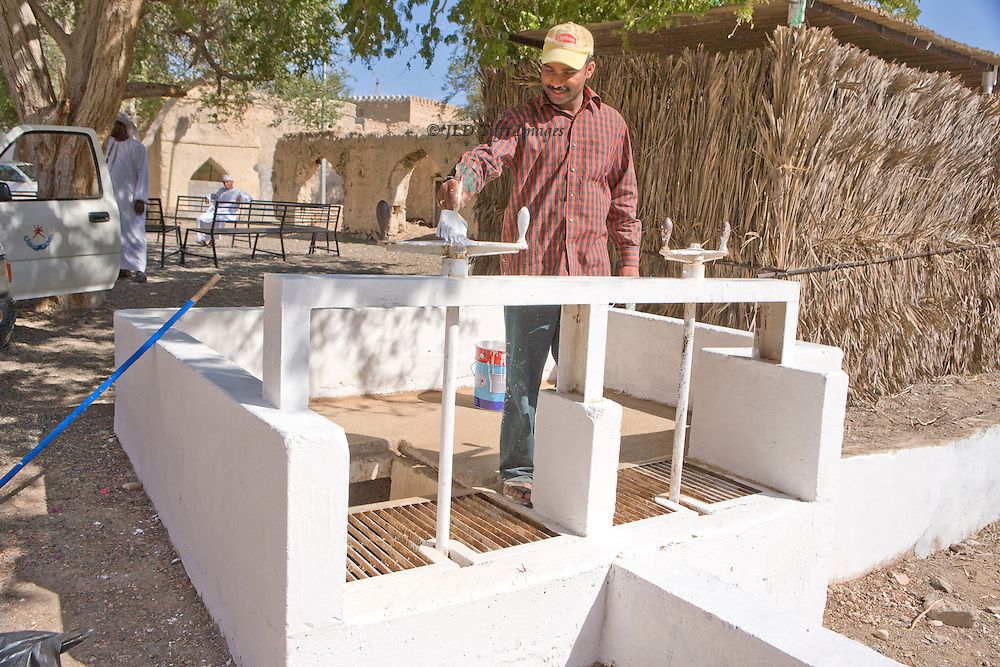 Oman, village of Al Mudayrib, a village of ancient mud brick houses kept in some repair and still occupied.  Workman freshly painting and whitewashing a falaj sluice.