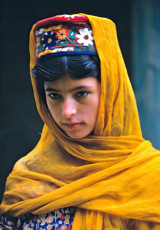 A Hunzakut girl is draped in a saffron-colored shawl, near Gilgit, Khyber Pakhtunkhwa, Pakistan.