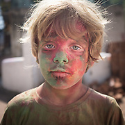 A child with his face covered with colors from Holi.