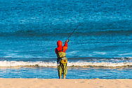 Spring Lake,NJ -- November 22, 2016. A fisherman casting his line into blue ocean water on a cold wintry day