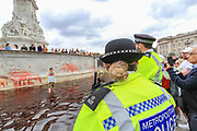 """Police arrived at the Victoria Memorial Fountain after Animal and climate activists, Animal Rebellion, dyed blood-red Buckingham Palace fountains on Thursday, Aug 26, 2021 - signifying as their statement said """"its' demonstrable role in hunting and animal agriculture"""". (VX Photo/ Vudi Xhymshiti)"""