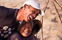 Fisherman and woman share a joke while sorting fish.