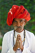 Traditional Namaste greeting from Indian man with traditional Rajasthani turban in village in Rajasthan, India. MODEL RELEASED