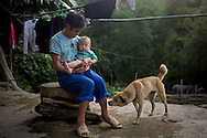 A Hmong man plays with his son and dog in front of their house in Lao Chai, Lao Cai Province, Vietnam, Southeast Asia