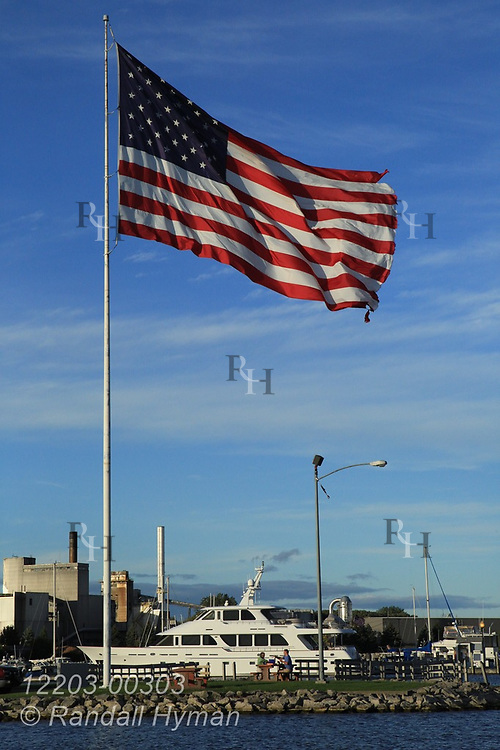 Large American flag flies over yacht marina on a brisk September afternoon in Alpena, Michigan.