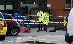 © London News Pictures. 27/03/2013 . London, UK.   Police stand over the body of a woman (left covered in red blanket) killed in a collision with a lorry on the corner of Chippenham Road and Harrow Road in London, on March 27, 2013. A shoe and red trolley can be seen next to the body. Photo credit : Ben Cawthra/LNP
