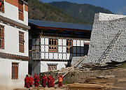 Young novice monks in brown robes in the courtyard of the state monastic school at Dechen Phodrung Monastery. They are below the whitewashed stone wall of the old Dzong. Thimpu, Druk Yul, Bhutan. 13 November 2007.