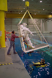 Stock photo of a man in his space suit being lowered into the pool at the NASA Neutral Buoyancy Lab in Houston Texas