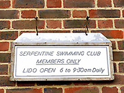 The sign outside the Serpentine Swimming Club changing room, Hyde Park, London, UK. The Serpentine Lake is situated in Hyde Park, London's largest central open space. The Serpentine Swimming Club was formed in 1864 'to promote the healthful habit of bathing in open water throughout the year'.  Its headquarters were beneath an old elm tree on the south side of the lake, a wooden bench for clothing being the only facility.  At this time London was undergoing rapid expansion and Hyde Park was now in the centre of a densely populated built up area and provided a place of relaxation to its urbanised masses. Now, the club has its own (somewhat spartan) changing facilities and members are  permitted by the Royal Parks to swim in the lake any morning before 09:30.  They race every Saturday morning throughout the year, regardless of the weather.