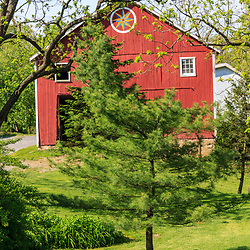 Hamburg, PA, USA- May 12, 2012: A Pennsylvania Dutch red barn with large round Hex sign in Berks County, PA.