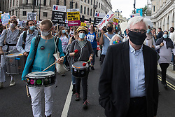 London, UK. 3rd July, 2021. John McDonnell, Labour MP for Hayes and Harlington, joins NHS workers and supporters taking part in a protest march from University College Hospital to Whitehall as part of a national day of action to mark the 73rd birthday of the National Health Service. The protesters called for fair pay for NHS workers, for better funding of the NHS and for an end to privatisation measures affecting the NHS.