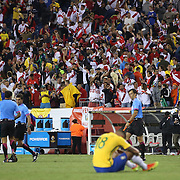 FOXBOROUGH, MASSACHUSETTS - JUNE 12:  Peru fans celebrate their sides shock 1-0 victory as Renato Augusto #18 of Brazil sits dejected on the field during the Brazil Vs Peru Group B match of the Copa America Centenario USA 2016 Tournament at Gillette Stadium on June 12, 2016 in Foxborough, Massachusetts. (Photo by Tim Clayton/Corbis via Getty Images)