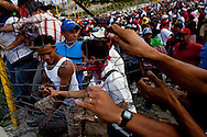 5 July 2009 - Tegucigalpa, Honduras - Supporters of ousted Honduras' President Manuel Zelaya dismantle a fence surrounding the Tegucigalpa airport in preperation for the arrival of Zelaya. President Zelaya was unable to land today, but pledged to return in the coming days. His supporters have been marching in the capital's streets since he was ousted last Sunday, but the protests have increased dramatically in the last few days.