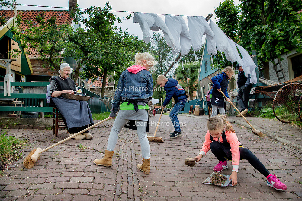 Nederland, Enkhuizen, 8 juni 2017.<br /> De stoep vegen zoals dat vroeger nog ging.<br /> Steeds meer scholen kiezen voor een educatie/leerzame schoolreis kiezen (ipv voor een pretpark).<br /> <br /> Foto: Jean-Pierre Jans