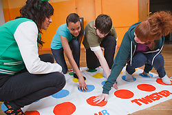 Teenagers doing Twister game in Youth Club. Cleared for Mental Health Issues.