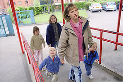 Single mother taking four young children to primary school,