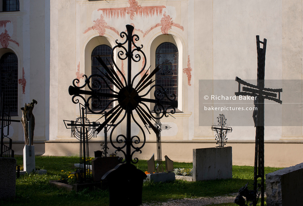 Typical Dolomites church architecture and graveyard ironwork in Leonhard-St Leonardo, a Dolomites village in south Tyrol, Italy.