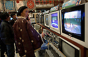 A Tibetan man shops for a new Television in a Lhasa shop.